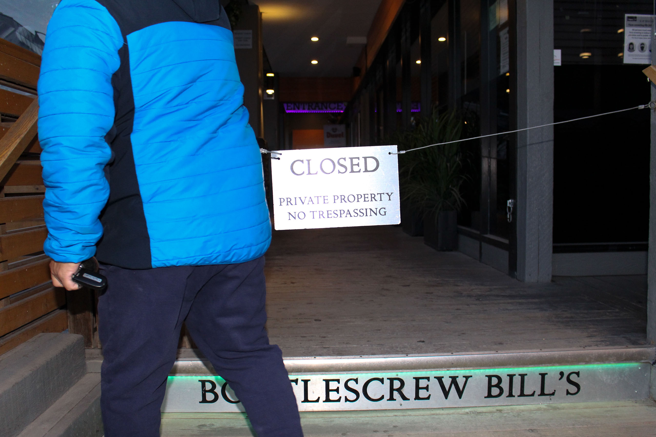 Francisco Melgar removes the closed fencing briefly before proceeding into Bottlescrew Bill's to clean in Calgary on April 15, 2021. Bottlescrew Bill's and Buzzard's is a bar in downtown Calgary on 10 Avenue S.W., and they have been open since 1980. They are known for their menu of beers from countries all around the world. (Photo by Alejandro Melgar/SAIT)